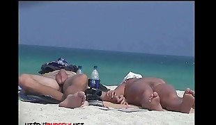 Bare tourists caught on beach spy cam loosening and enjoying